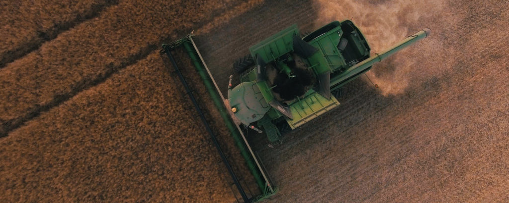 green farming equipment on brown field